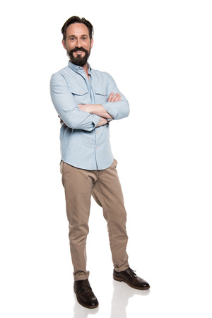 smiling man in casual clothes standing with crossed arms and looking at camera isolated on white