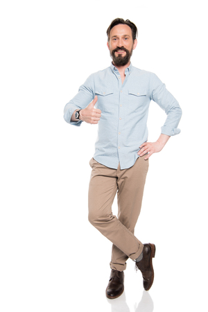 bearded middle aged man standing with hand on waist and showing thumb up