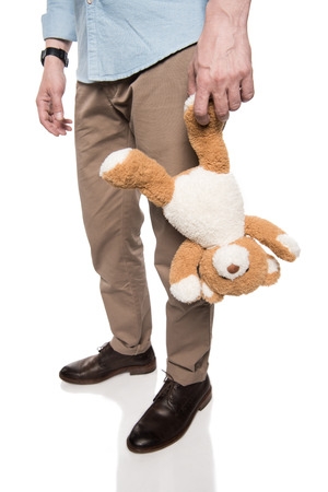 casual man holding teddy bear isolated on white Stock Photo