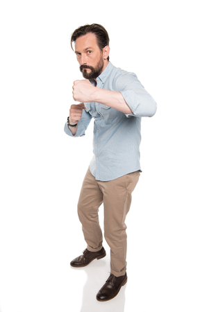 bearded man standing in boxing pose and looking at camera