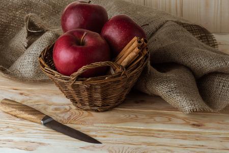 fresh organic red apples and cinnamon sticks in wicker basket Фото со стока