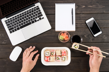 Top view of laptop with computer mouse, blank notebook with pen, smartphone and sushi set