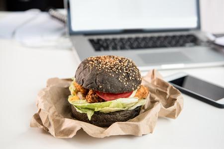 close up of tasty burger with black bun