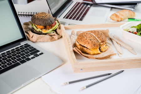tasty burgers with fresh salad and bread loaf with laptops
