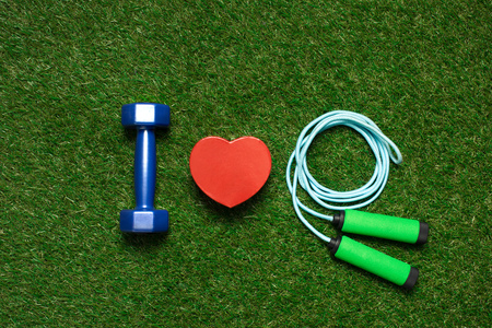 colorful dumbbell with heart symbol and skipping rope