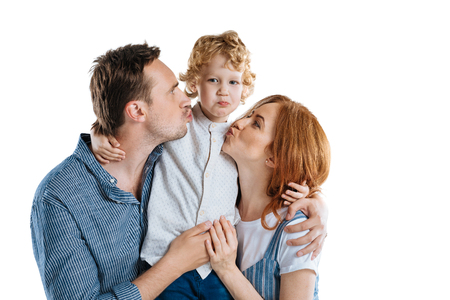 Happy family with one child hugging and smiling at camera