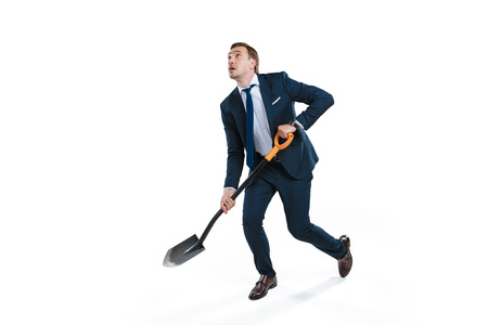young businessman in formal wear digging with shovel and looking up
