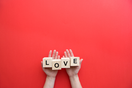 Human hands holding wooden cubes with love sign isolated on red background