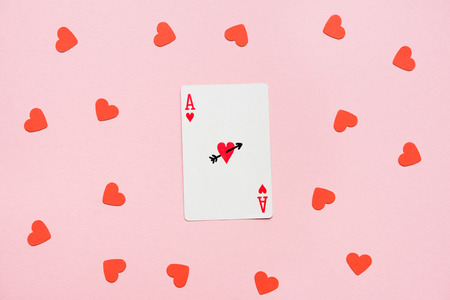 Heart ace of playing card with red hearts lying around on pink surface Zdjęcie Seryjne