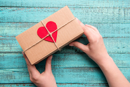 Above view of human hands holding gift box with red heart on the top on wooden table