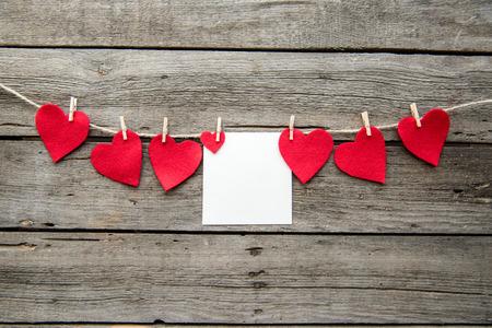 Rode hart papier gesneden en wenskaart met wasknijpers op houten achtergrond