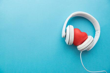 青い表面上の真ん中の赤いハートに白いヘッドフォンに署名します。