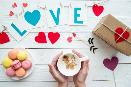 Top view of human hands holding cup of cappuccino with macaroon cookies, romantic decoration on wooden background. Valentines day composition