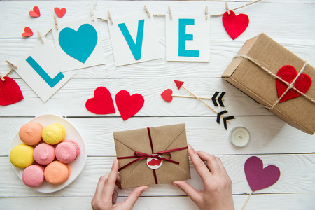 Above view of hands preparing gifts for Valentines day celebration with decorations and macaroons around on the table Stok Fotoğraf - 81317473