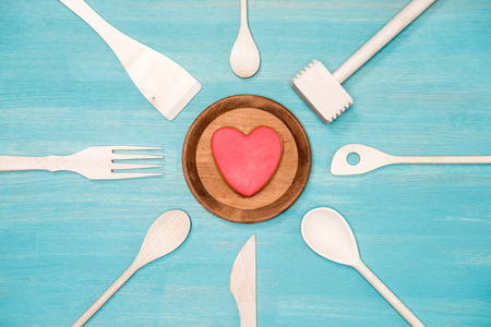 top view of various wooden cooking utensils with heart symbol on plate Stock Photo