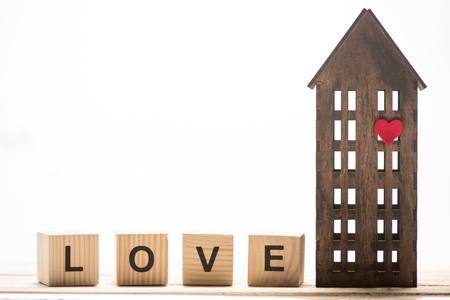 Wooden block cubes with love sign and wooden house model isolated on white