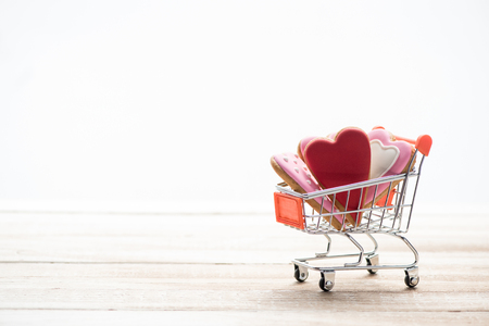 anniversary sale: Shopping trolley full of heart shaped cookies with copy space Stock Photo