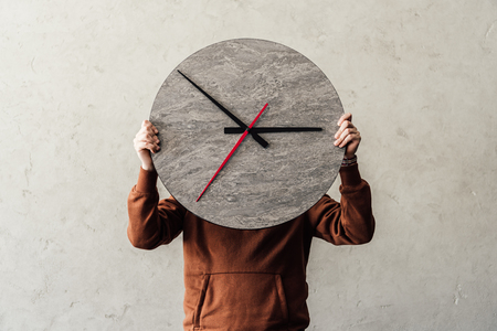 Unrecognizable person covering face with stylish round wooden clock Stock Photo