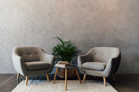 Zwei gemütliche graue Lehnsessel, die auf weißem Teppich im leeren Raum stehen Standard-Bild - 81318065