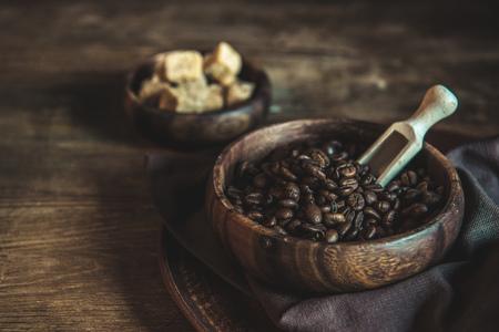 Koffiebonen en bruine suiker in kommen op houten tafelblad Stockfoto - 81318080