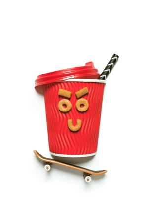 Tasse à café jetable rouge avec une drôle de tête faite de biscuits et petit skateboard Banque d'images - 81318081