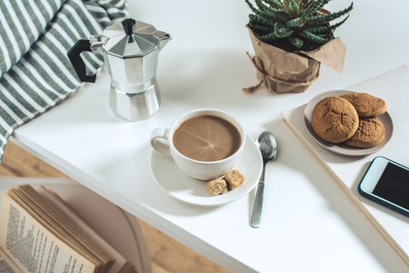 coffee cup with cookies and potted plant with smartphone on tabletop