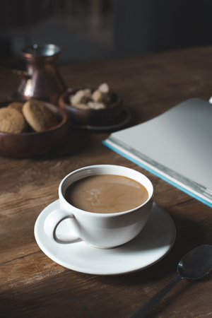 close up of coffee cup with empty book on wooden tabletop