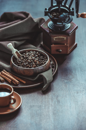 coffee with vintage grinder and beans in bowl on wooden tabletop