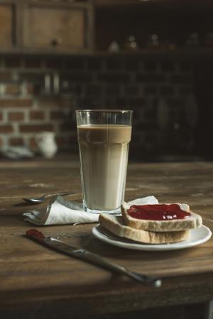 ラテ ガラス、パン皿の上のジャムと木製のテーブルの上の食器