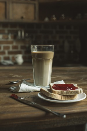 latte in glass, bread with jam on plate and cutlery on wooden tabletop