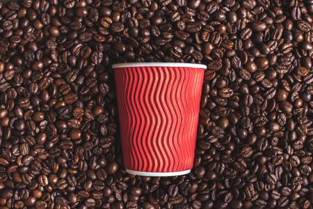 コーヒー豆の焙煎に横たわっている赤いプラスチック カップのクローズ アップ