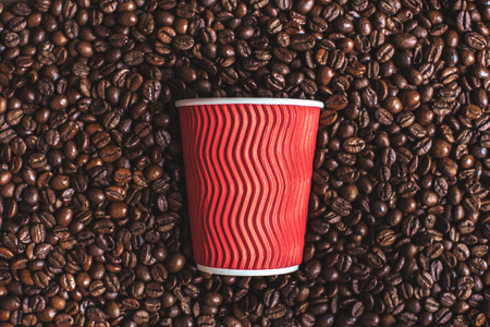 close up of red plastic cup lying on roasted coffee beans