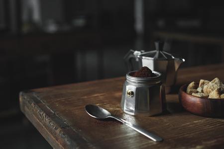 ボウルに木製のテーブルの上のコーヒーと茶色の砂糖と金属食器 写真素材