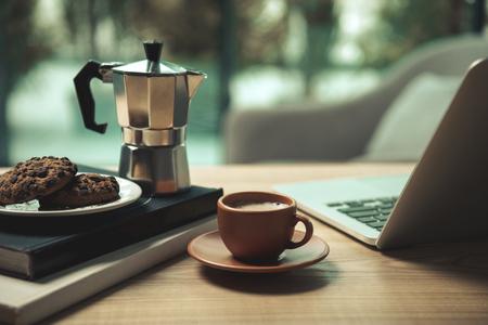 ノート パソコン、コーヒー、萌香のポットと木製のテーブルに書籍とチョコレート チップ クッキーのクローズ アップ ビュー