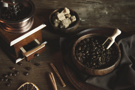 coffee grinder with beans and brown sugar in bowls on wooden tabletop