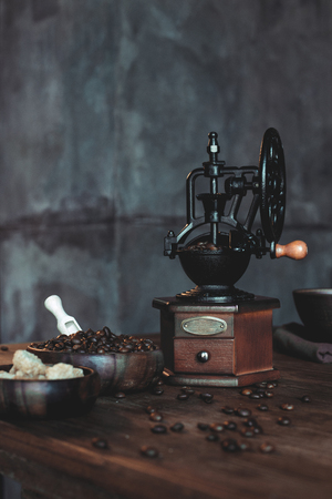 vintage coffee grinder with beans and brown sugar in bowls on wooden tabletop