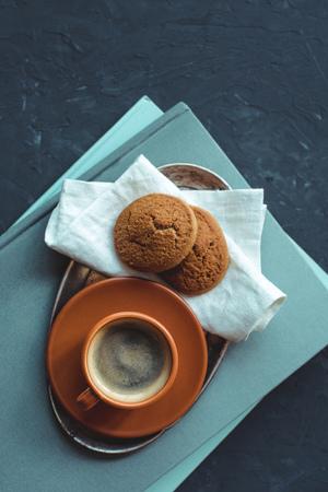 布や卓上に本にクッキーとコーヒーのトップ ビュー 写真素材