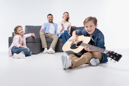 parents et mignon petite soeur en jouant au sourire garçon jouant de la guitare Banque d'images
