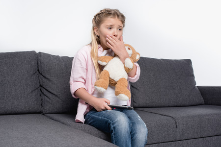 little girl with teddy bear feeling scared while watching tv
