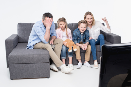 family sitting on sofa and watching tv together