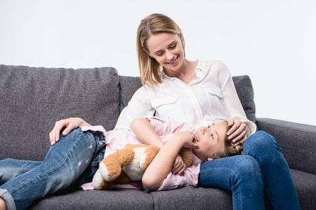 소파에 함께 앉아 작은 딸과 함께 웃는 어머니 스톡 콘텐츠 - 82065567