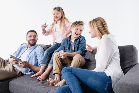 happy interacting caucasian family sitting on sofa together Stock Photo