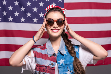背後にアメリカの国旗とサングラスでスタイリッシュな女性を笑顔