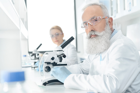 Professional chemists in white coats working with microscopes in laboratory Stock Photo