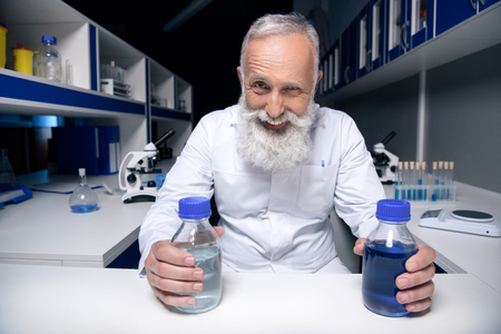 smiling scientist holding bottles with reagents in hands in laboratory 版權商用圖片