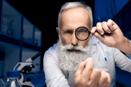focused scientist looking at hand through magnifying glass in laboratory