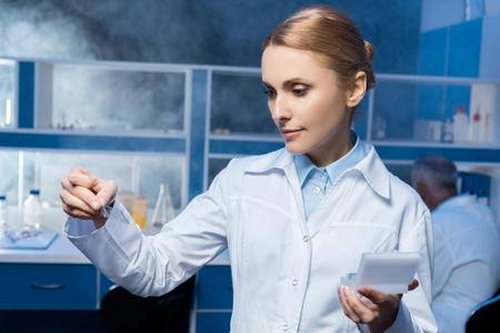 pensive chemist in lab coat looking at samples 版權商用圖片