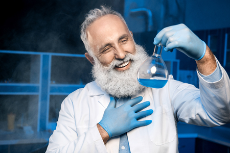 mature scientist in lab coat holding flask with reagent at laboratory