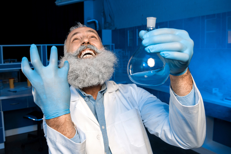 grey haired scientist celebrating success of scientific experiment and holding flask with reagent
