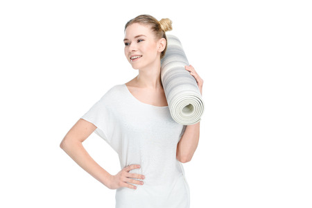 attractive blonde girl in white sportswear holding yoga mat Stock Photo
